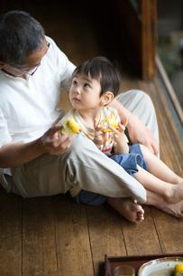 縁側でとうもろこしを食べる祖父と孫の写真素材 [FYI03246747]