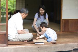 縁側で祖父と将棋に向かう孫の写真素材 [FYI03246752]