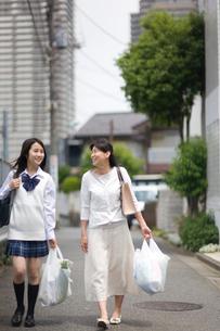 買い物袋を持った母親と娘の写真素材 [FYI03246754]