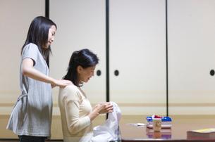 裁縫する母親の肩をもむ娘の写真素材 [FYI03246763]