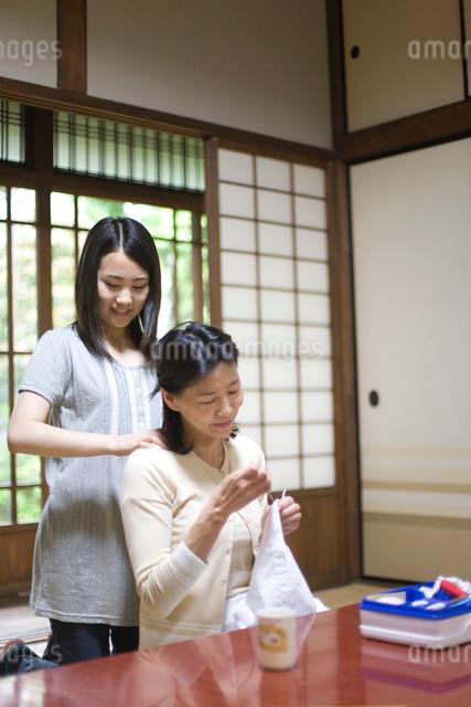 裁縫する母親の肩をもむ娘の写真素材 [FYI03246792]