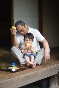 縁側でとうもろこしを食べる祖父と孫の写真素材 [FYI03246813]