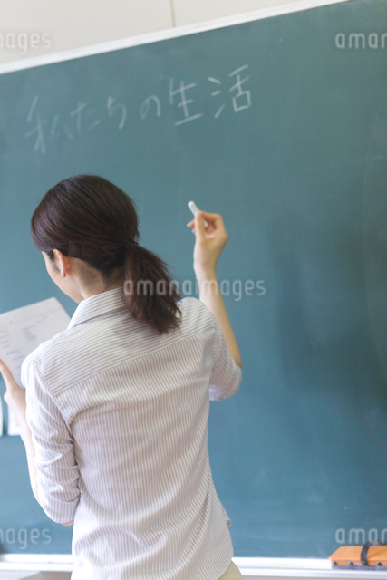 黒板に字を書く小学校の先生の写真素材 [FYI03246816]