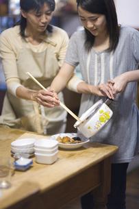 煮物をよそう娘を手伝う母親の写真素材 [FYI03246837]