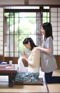 裁縫する母親の肩をもむ娘の写真素材 [FYI03246841]