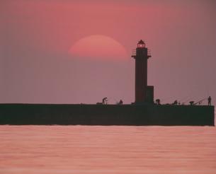 夕日と灯台とつり人の写真素材 [FYI03246984]