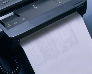 FAXと流れ出る用紙の写真素材 [FYI03248817]