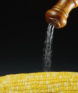 トウモロコシに塩をかけるの写真素材 [FYI03249000]