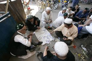 トルファンの市場でカードゲームをする人々の写真素材 [FYI03313095]