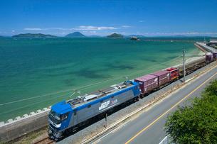 JR予讃線貨物列車と瀬戸内海の津嶋神社の写真素材 [FYI03315133]