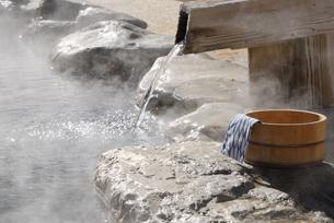 湯けむり立つ露天風呂の湯口と手桶の写真素材 [FYI03317257]