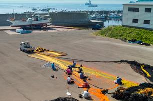 魚網を修復中の尻屋漁港を望むの写真素材 [FYI03343188]