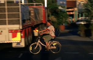 潮風が吹く夕暮れの街を走る自転車の写真素材 [FYI03344136]