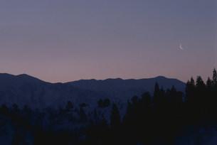 巻機山の夕暮れにかかる上弦の月の写真素材 [FYI03344148]