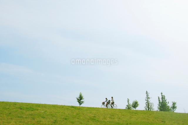 自転車で土手を走る女子高生の写真素材 [FYI03347910]