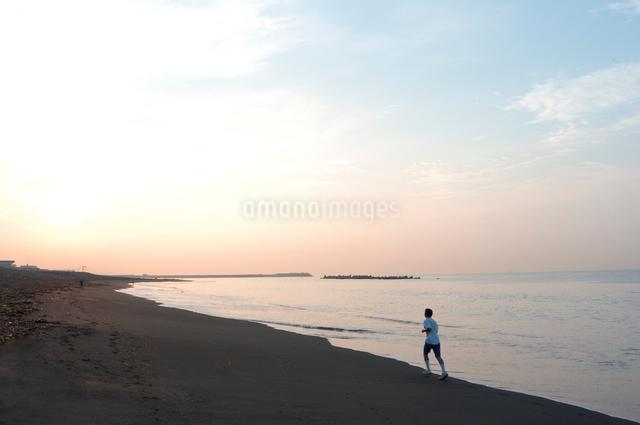 早朝の砂浜をランニングする人の写真素材 [FYI03347912]