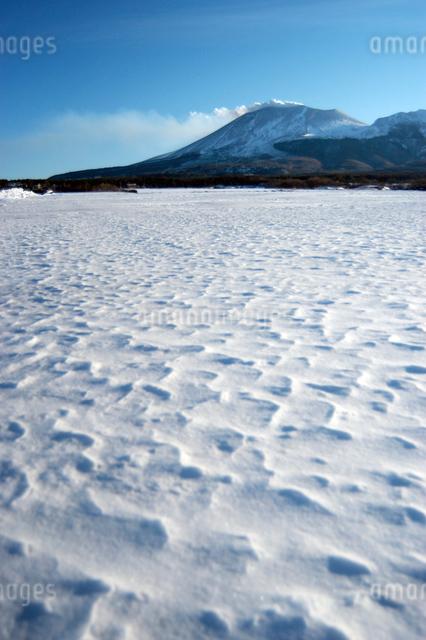 噴煙を吐く浅間山と雪原の写真素材 [FYI03347940]