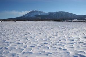 波打つ雪原と噴煙を上げる冬の浅間山の写真素材 [FYI03348011]