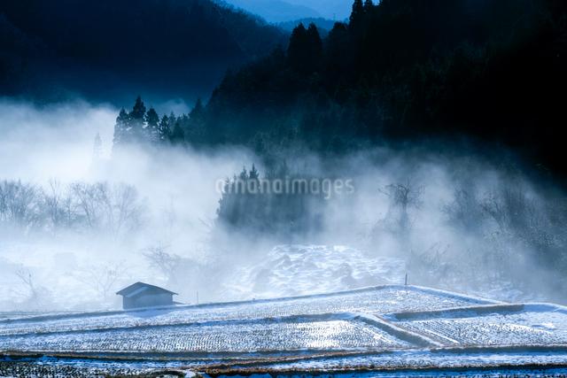 谷霧に浮かぶ冬の棚田と農小屋の写真素材 [FYI03348302]