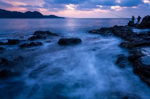 黄昏時の岩礁と釣り人の写真素材 [FYI03348375]