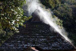 蒸気霧立ち昇る茅葺屋根の写真素材 [FYI03348439]