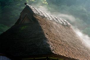 蒸気霧立ち昇る茅葺屋根の写真素材 [FYI03348516]