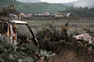 廃車と集落の写真素材 [FYI03348548]