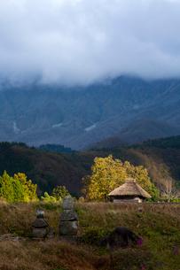 雲間の朝日に映える茅葺の納屋の写真素材 [FYI03348831]