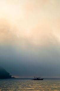 網を引く明け時の漁船の写真素材 [FYI03349884]