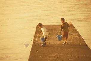 堤防で網とバケツを持つ2人の少年の写真素材 [FYI03351230]