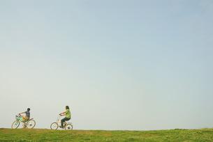 自転車で土手を走る少年と父親の写真素材 [FYI03351259]