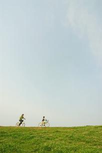 自転車で土手を走る少年と父親の写真素材 [FYI03351260]