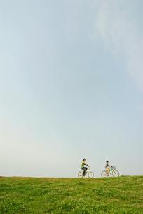 自転車で土手を走る少年と父親の写真素材 [FYI03351262]