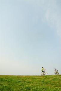 自転車で土手を走る少年と父親の写真素材 [FYI03351264]