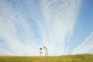 風船を持って歩く少年と少女の写真素材 [FYI03351266]