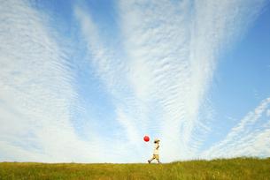 風船を持って土手を歩く少年の写真素材 [FYI03351269]