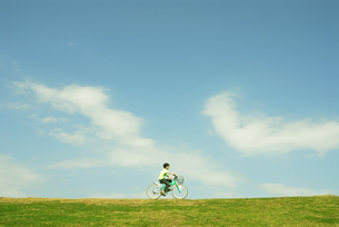 土手を自転車で走る男の子の写真素材 [FYI03351300]
