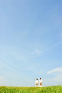 白いイスに座る2人の女の子と青空の写真素材 [FYI03351323]