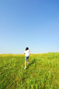 草原を走る女の子の後姿の写真素材 [FYI03351328]