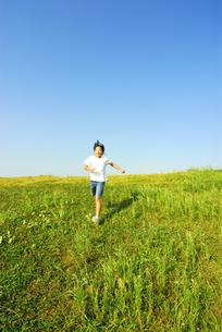 草原を走る女の子の写真素材 [FYI03351333]