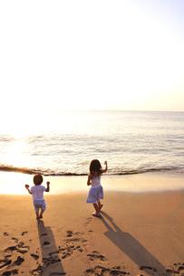 夕景の海岸で遊ぶ子供たちの写真素材 [FYI03351382]