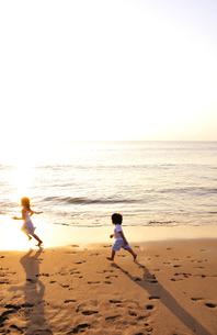 夕景の海岸を走る子供たちの写真素材 [FYI03351383]