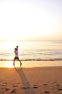 肩車をして夕景の海を歩く親子の写真素材 [FYI03351391]