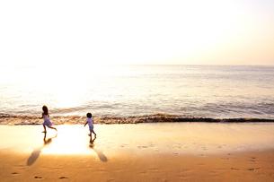 夕景の海岸を走る子供たちの写真素材 [FYI03351407]