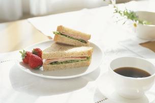 コーヒーとハムサンドイッチと苺の朝食の写真素材 [FYI03351411]