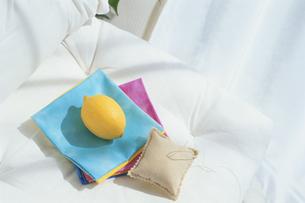 ソファの上に置かれた布と針山とレモンの写真素材 [FYI03351417]