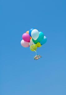 風船に運ばれるギフトボックスの写真素材 [FYI03352198]