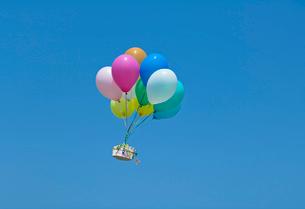 風船に運ばれるギフトボックスの写真素材 [FYI03352207]