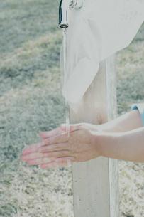 公園の蛇口と洗っている手の写真素材 [FYI03353133]