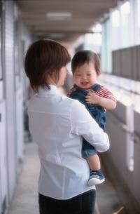 マンションの廊下で母親に抱かれる日本人の男の子の赤ちゃんの写真素材 [FYI03353295]